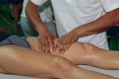 Massagem dos músculos do ` s do atleta após o exercício do esporte Imagem de Stock