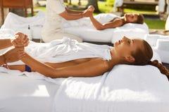 Massagem dos termas Pares que apreciam relaxando a massagem da mão fora fotos de stock