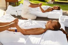 Massagem dos termas Pares que apreciam relaxando a massagem da mão fora imagens de stock royalty free
