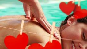 Massagem no lado da piscina com corações de papel vermelhos bonitos para o dia de são valentim video estoque