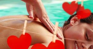 Massagem no lado da piscina com corações de papel vermelhos bonitos para o dia de são valentim 4k video estoque
