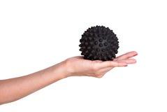 Massagem pontudo preta da bola em uma mão fêmea foto de stock royalty free