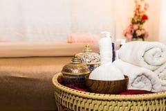 Massageobjektet och Spa oljer i korg på säng Royaltyfri Fotografi