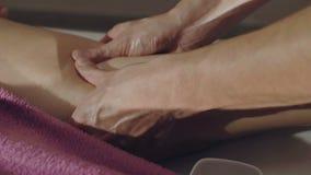 Massager wärmt weibliches Bein in einer Behandlung 4K auf stock video