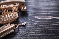 Massagers and nailbrush on vintage wooden board Royalty Free Stock Photo