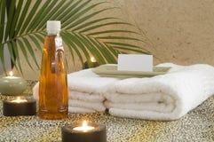 Massageschmieröl mit Kerzen und Palmenzweig lizenzfreie stockfotos