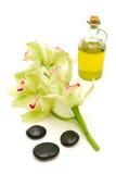 Massageschmieröl und -steine mit Orchideen Lizenzfreies Stockbild