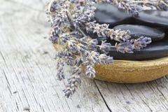 Massagestenar och torkad lavendel Arkivfoto