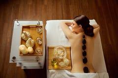 Massagestenar på baksida av en kvinna på brunnsortsalongen royaltyfria foton