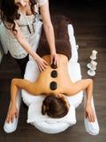 Massageterapeut som applicerar en varm stenmassage Arkivfoto