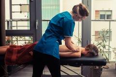 Massageterapeut som behandlar patienten royaltyfri foto