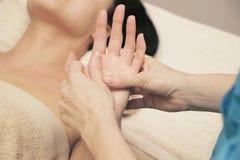 Massageterapeut som gör en terapeutisk handmassage för en kvinna royaltyfri foto
