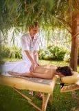 Massageterapeut som gör en tillbaka massagekvinna i natur arkivbild