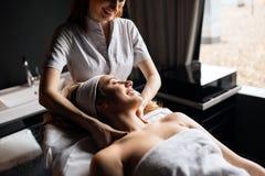 Massageterapeut som masserar kvinnan royaltyfri bild