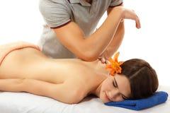 Massaggi giovane bello allegro della donna posteriore isolato su bianco immagini stock