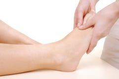 Massaggi i piedi di giovane donna Immagine Stock