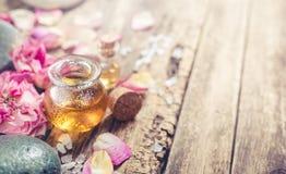 Massaggi il petrolio, i fiori dei petali e le pietre di zen Fotografia Stock Libera da Diritti