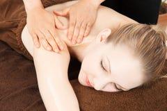 Massaggi una giovane donna Fotografie Stock Libere da Diritti