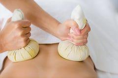 Massaggiatore che dà massaggio di erbe della compressa alla donna Fotografia Stock