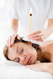 Massaggiatore che dà trattamento della candela dell'orecchio alla donna fotografie stock