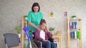 Massaggiatore di medico che fa massaggio del collo ad un adolescente in una sedia a rotelle archivi video