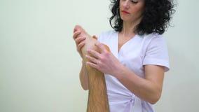 Massaggiatore femminile in uniforme che fa massaggio del piede per il cliente maschio nel salone della stazione termale stock footage