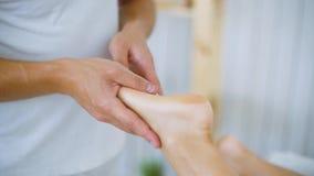 Massaggiatore maschio che massaggia il piede della gamba della giovane donna delle mani sulla tavola nel salone della stazione te video d archivio
