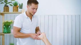 Massaggiatore maschio del ritratto che massaggia il bello piede della gamba della giovane donna sulla tavola nel salone della sta stock footage