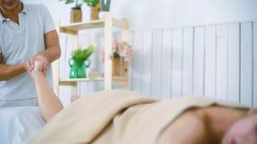 Massaggiatore maschio del ritratto che massaggia il bello piede della gamba della giovane donna sulla tavola nel salone della sta video d archivio