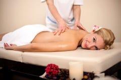 Massaggiatore professionista che fa massaggio della parte posteriore della femmina nella bellezza Fotografia Stock Libera da Diritti