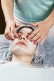 Massaggiatrice che fa massaggio di fronte Fotografia Stock