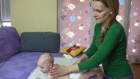 Massaggiatrice che massaggia la piccola parte posteriore del bambino sullo strato Cura del bambino video d archivio