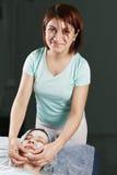 Massaggiatrice sorridente che fa massaggio di fronte Immagini Stock