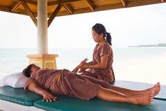 Massaggiatrice sul lavoro sulla spiaggia in Tailandia Fotografia Stock