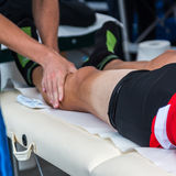 Massaggio dei muscoli dell'atleta dopo l'allenamento di sport Fotografia Stock Libera da Diritti
