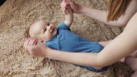 Massaggio del bambino Madre che fa ginnastica al bambino Bambino neonato e mamma a letto archivi video