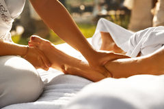 Massaggio del corpo alla stazione termale Chiuda sulle mani che massaggiano le gambe femminili fotografia stock