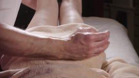 Massaggio del piede di benessere Chiuda su dell'osteologo che fa il massaggio manipolatore Mani dell'uomo che massaggiano femmina archivi video