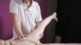 Massaggio del piede di benessere Chiuda su dell'osteologo che fa il massaggio manipolatore Mani dell'uomo che massaggiano femmina stock footage
