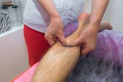 Massaggio del piede Fisioterapista della massaggiatrice che dà massaggio della gamba ad un uomo in clinica Fine in su Immagini Stock Libere da Diritti