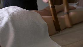Massaggio del piede nel salone della stazione termale con i bastoni di bambù Primo piano delle gambe, massaggio brasiliano stock footage