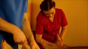 Massaggio del piede per le coppie nell'atmosfera calda del salone stock footage