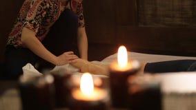 Massaggio del piede in studio tailandese Terapista professionista che dà massaggio tailandese tradizionale chiuda sulle candele stock footage