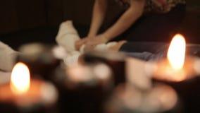 Massaggio del piede in studio tailandese Terapista professionista che dà massaggio tailandese tradizionale chiuda sulle candele video d archivio