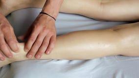 Massaggio dell'olio del primo piano della gamba di una ragazza stock footage