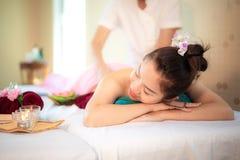 Massaggio della linfa Il massaggiatore che fa il massaggio con lo zucchero del trattamento sfrega sull'ente asiatico della donna  immagine stock libera da diritti