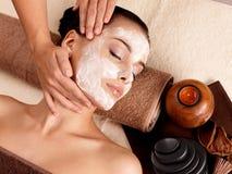Massaggio della stazione termale per la donna con la maschera facciale sul fronte Fotografie Stock