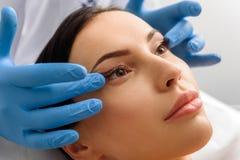 Massaggio di fronte di presa femminile estraneo nella cosmetologia Fotografia Stock Libera da Diritti