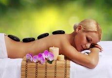 Massaggio di pietra della stazione termale. Donna bionda Fotografie Stock Libere da Diritti