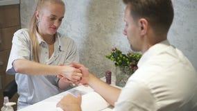 Massaggio di rilassamento della mano dalla donna attraente al negozio di bellezza per il cliente attraente video d archivio